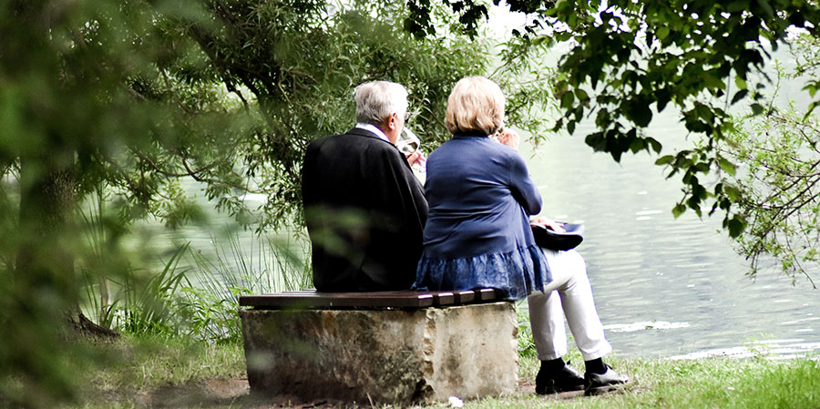 An old couple enjoying a drink and the view of a river